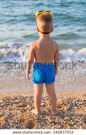Kid in diving mask standing on the beach and looking to sea - stock photo
