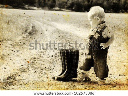kid  in harvested field. Photo in old image style. - stock photo