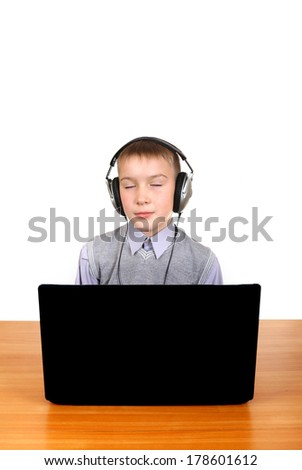Kid in Headphones at the Desk with Laptop Isolated on the White - stock photo