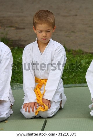kid in karate suit with yellow belt on competition - stock photo