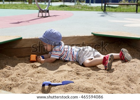 Kid in panama hat crawling in sandbox