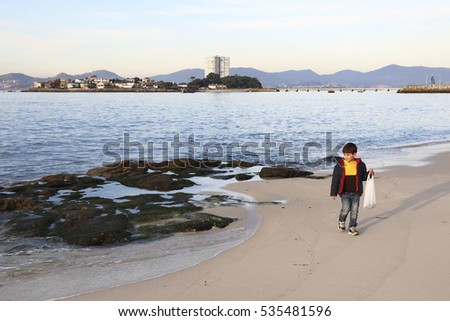 kid in the beach with a plastic bag looking for little treasures