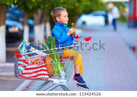 kid in trolley full of foodstuffs after shopping - stock photo