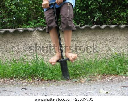 Kid jumping on kangaroo stick - stock photo
