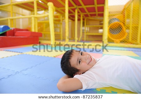 Kid laying on ground in the kindergarten - stock photo