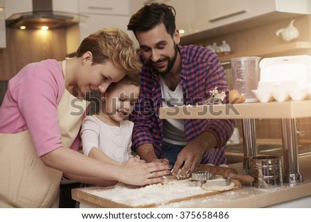 Kid loves spending time with her parents in the kitchen - stock photo