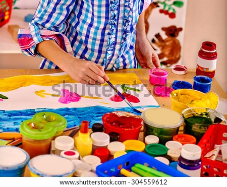 Kid making decoration card with bow. Children pictures in school. - stock photo