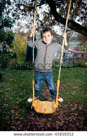 Kid on a swing - stock photo