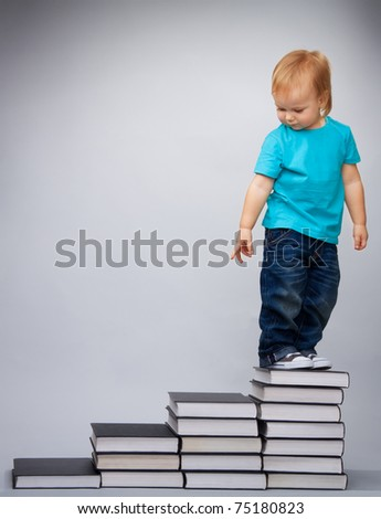 Kid on top of early education leader made of pile of books standing and looking back - stock photo