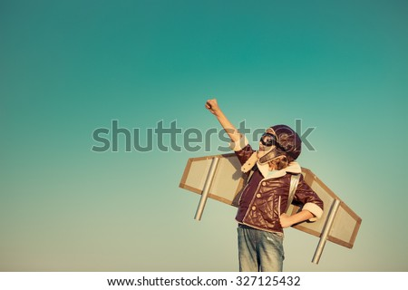 Kid pilot with toy jetpack against autumn sky background. Happy child playing outdoors - stock photo