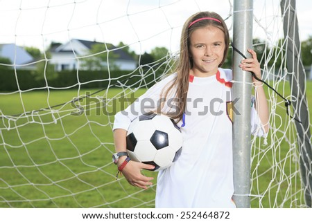 Kid play soccer on a field - stock photo