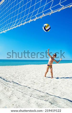 Kid play volleyball on sea beach, Ukraine - stock photo