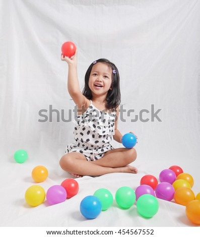 Kid play with color ball on white back ground