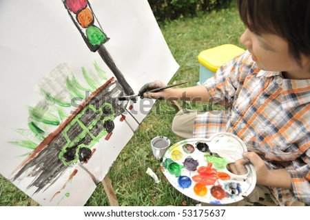Kid playing and drawing outdoor, traffic light - stock photo