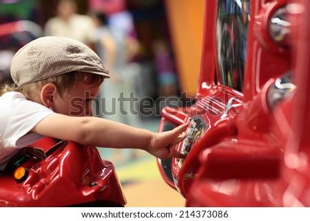 Kid playing arcade game machine at an amusement park - stock photo