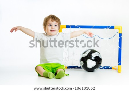 kid playing football and sitting in front of the gate - stock photo