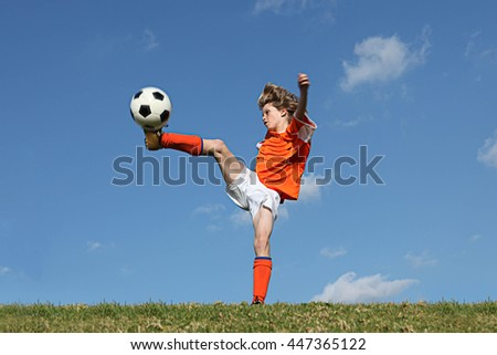 kid playing football or soccer kicking ball  - stock photo