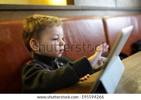 Kid playing on a Tablet PC in the restaurant - stock photo