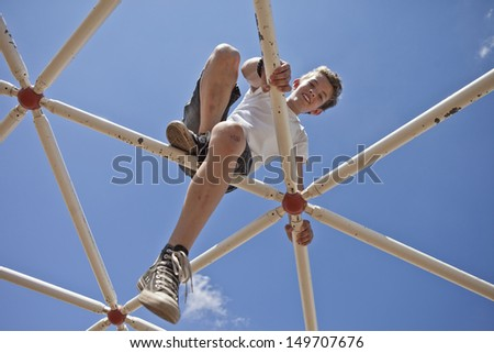 kid playing on monkey bars, view toward blue sky - stock photo