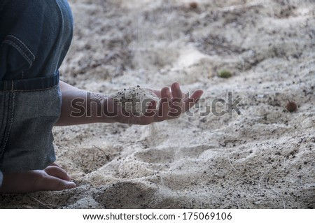 Kid playing sand on the beach. - stock photo