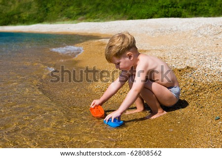 kid playing with colorful toys on the beach - stock photo