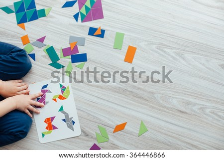 Kid playing with geometric shapes on the floor with copy space - stock photo