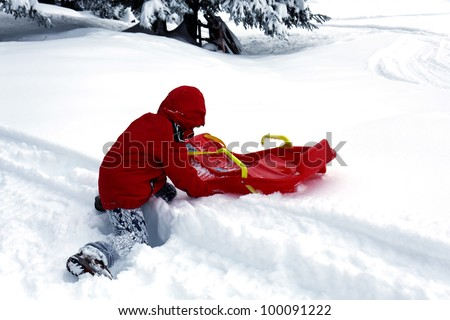 Kid playing with his snow sled