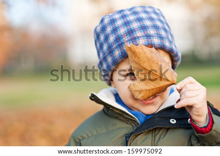 Kid playing with leaf outside in a park in autumn. - stock photo