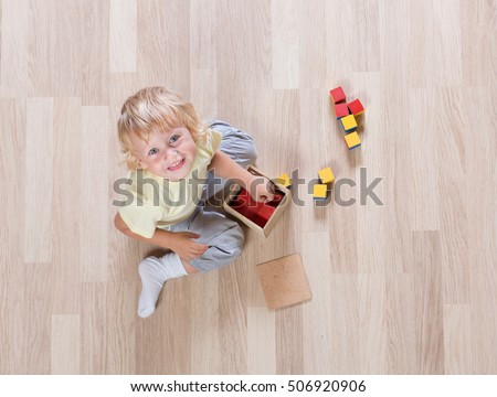 Kid playing with toys on floor top view