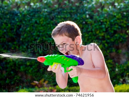 Kid playing with water toy in the summer. - stock photo