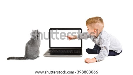 Kid points finger at the screen of laptop sitting with a cat isolated on a white background - stock photo