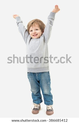 Kid raised his hands to the top. Full length. Gray no image sweater and blue jeans.  Mockups template - stock photo