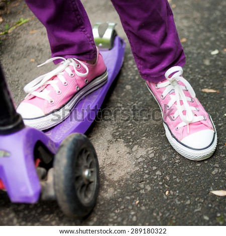 Kid riding a scooter in an urban neighborhood. Feet wearing sneakers close up.  - stock photo