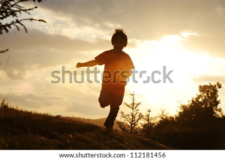 Kid running on meadow silhouette - stock photo
