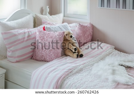 kid's bedroom with doll and pink pillows on bed at home - stock photo