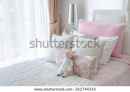 kid's bedroom with doll on bed in pink color style at home - stock photo