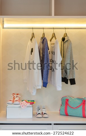 kid's clothes hanging on rack with shoes and socks in wardrobe - stock photo
