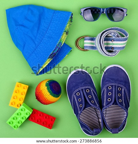Kid's street outfit and some toys on green background. Overhead view. Teen's concept.