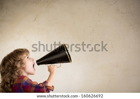 Kid shouting through vintage megaphone. Communication concept. - stock photo