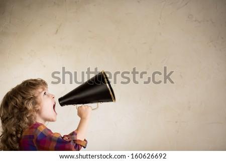 Kid shouting through vintage megaphone. Communication concept. - stock photo