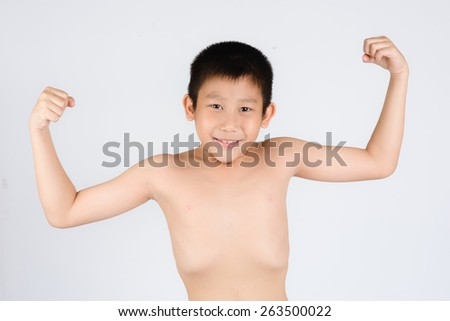 kid showing his muscles isolated on gray background - stock photo
