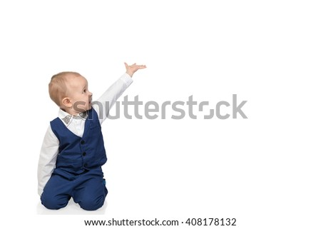Kid sits and shows in side - stock photo