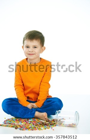 Kid sitting cross-legged on floor with sweets jar spilled. Happy, looking at camera, isolated on white. - stock photo