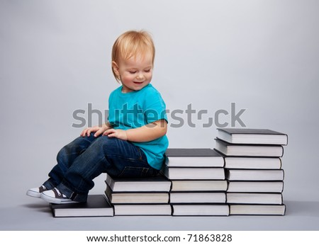 Kid sitting on a a steps made of books and laughing - stock photo
