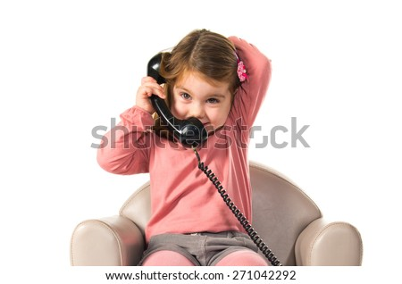 Kid sitting on armchair talking with vintage phone - stock photo