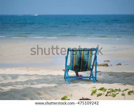 Kid sitting on beach chair and looking to the blue sea