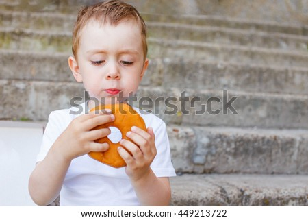 kid sitting on the steps with a donut in hands. little boy is looking forward to eating a donut. copy space for your text - stock photo