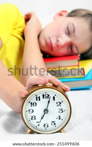 Kid sleep with Alarm Clock on the Bed. Focus on the Clock - stock photo