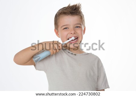 kid smiles while brushing his teeth - stock photo