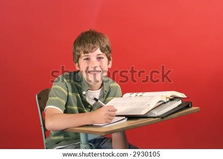 kid smiling at desk - stock photo